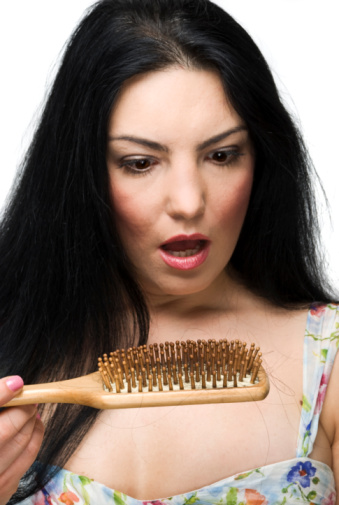 Shocked woman loss hair on hairbrush
